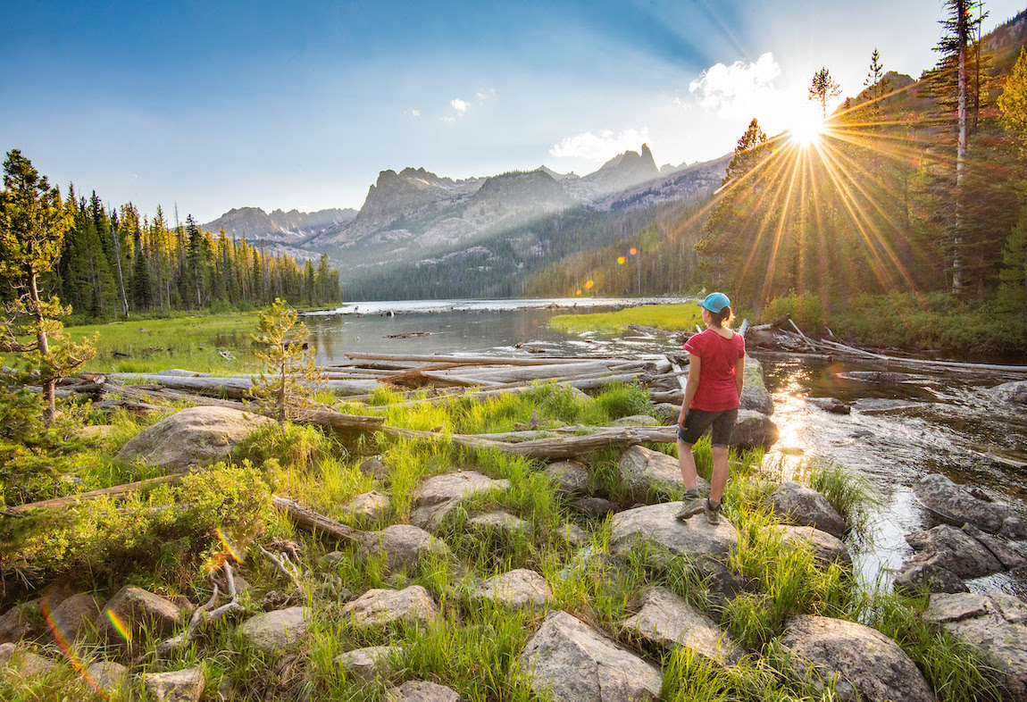 female hiker watches the sunset while standing on rocks near the Sawtooth Mountains in Idaho